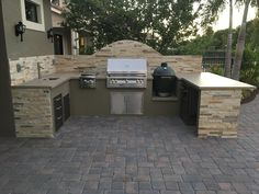 "Custom outdoor kitchen with Alfresco ALXE 36"" grill, double side burner, Big Green Egg and Dekton countertop"