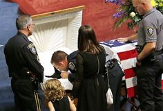 Oklahoma City police officer Sgt. Ryan Stark, center, leans over the casket of his canine partner, K-9 Kye, following funeral services for t...