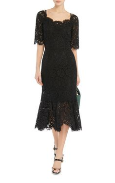 Finely crafted in Italy, this **Dolce & Gabbana** dress features a lace body and ruffled hem skirt with scalloped edging.