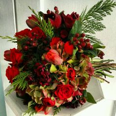 Winter Bridal Bouquet. Antique hydrangea, red tulips, red spray roses, hypericum berries, winter greens.