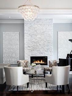 Bling chandelier hangs in front of modern grey stone fireplace #GlitterRoom