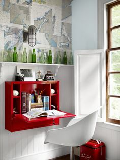 """This space-saving, schoolhouse-red desk folds up when not in use and can be repurposed in multiple ways: as a cocktail bar, craft station, or, if you equip it with a mirror, a vanity. For a similar look, try the """"wallbanger"""" shelf at Bobby Berk Home ($399; enter code CL10 for a 10% reader discount)."""