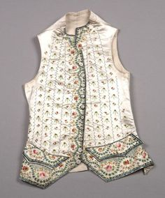 Man's winter waistcoat Date: ca. 1775 Media: Embroidered Silk Satin, Cotton, Wool Flannel Lining Country: France Accession Number: 2005.96.1 Winter waistcoat of white silk satin with overall and border embroidery of polychrome flowers and foliage. Small stand collar, 10 embroidered self buttons. Backed in white cotton and lined with cream wool flannel.