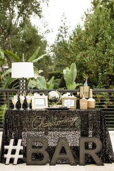 "A fabulous cocktail station featuring a black sequined tablecloth, a gold wire ""Chardonnay"" sign, a black quatrefoil lamp, gilded liquor bottles, and giant marquee letters. 