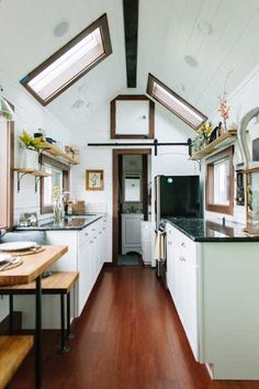 The cook space inside this Tiny Heirloom home could pass for a high-end galley kitchen in a New York City apartment! The granite countertops are part of the basic package. The sliding barn-style door to the bathroom and open shelving are stylish as well as space-efficient. | Photo: Ian Pratt with dwightly.com