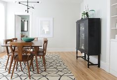 Wood table & chairs on ivory & black rug over light wood floors, white walls, with black china cabinet  The Dining Room - Design Crush