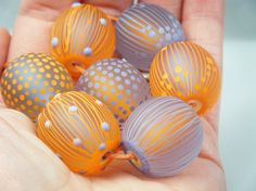 This set has 7 extra large round beads each large enough to use as a focal measuring 20mm-21mm and all were wound on 2mm mandrels. The colours used are several shades/ combinations of lilac and orange. All are etched.
