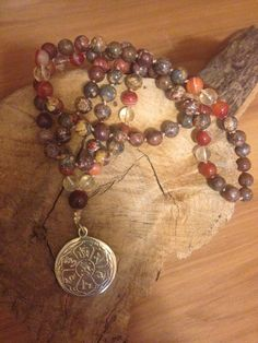 This is a beautifully handcrafted mala of Leopard Jasper, Amber Agate and Citrinestones. Jasper solidifies and grounds, encouraging practical solutions. it energizes and protects. Amber Agate corrects imbalances in the nervous system, which makes it ideal for detoxification. Citrine increases self confidence, optimism and awareness. Stones are 8mm with aMani Padme pendant.    Root Chakra/Solar Plexus Chakra | Shop this product here: http://spreesy.com/dhyanabydawn/18 | Shop all of our…