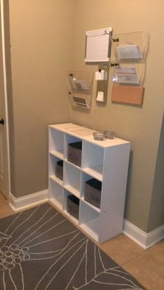 Just what I want for my house: items left around the house go into the person's bin. At the end of the day, they can put their own things away.  Space above for a calendar, and folders to collect papers to be filed, mail to be opened, etc.