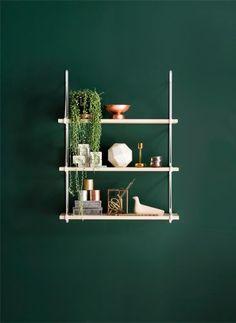 Pared en verde oscuro con contraste de mobiliario y objetos decorativosen tonos claros