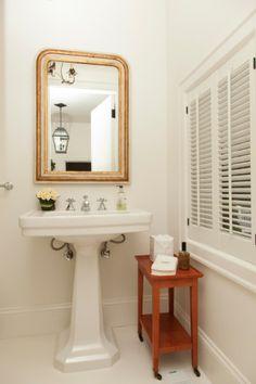 Banheiro pequeno branco com mesinha de madeira