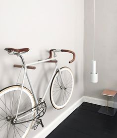 an amazing way of haning up your bike, wall hooks in wood for displaying your cool bike in the living room - Hege in France