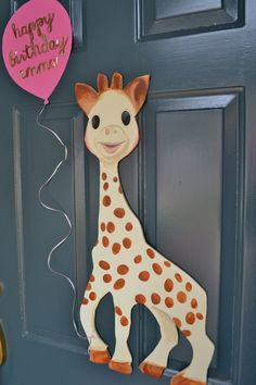 Sophie Giraffe First Birthday Party: draw out giraffe and place inside a yarn wrapped wreath on door.
