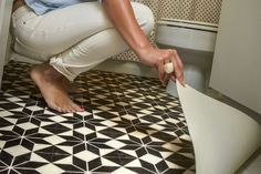 Kerra Michele, concealed hers using a water resistant vinyl floor cloth that she custom cut to fit.      You can also use interlocking rubber floor tiles. They're available in lots of colors, and the type with raised dots resembles ceramic penny round tile. To secure in place, use carpet tape.