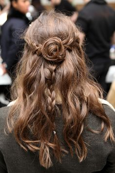 Hair backstage at Rodarte, Fall 2013. Two braids into a bun with a hanging braid half up half down