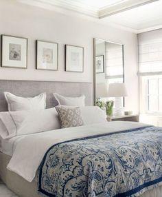decoração de quarto de casal com espelho grande na lateral da cama, trio de quadros na parede da cabeceira: