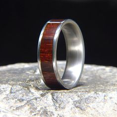 7 mm wide titanium comfort fit band, with a 5 mm Brazilian rosewood inlay 100 yr+ old growth pre-ban brazilian rosewood which varies in coloration from a deep chocolate to medium brown and the highly sought after burgundy hues like this one are very expensive and getting extremely hard