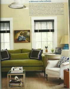 Really like the feel of this room.  Great shade of (olive?) green on the velvet sofa.  Love the blue pillow on the white slipcovered chair.  Wood blinds mounted in old windows surrounded by neutral cream walls.  Great mix of vintage, classic and modern.