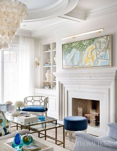 Next to the fireplace, a white-painted, open-back chair and an ottoman covered in Schumacher fabric nestle beneath a painting by America Martin. - Photo: Emily Jenkins Followill / Design: Melanie Turner