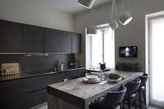 Dark kitchen with raw wood dining table. love the lights//