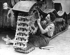 A British war effort worker adjusts the tracks on a tank, 1940.