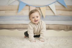one year old boy smiling in cream sweater on blue and tan backdrop - watertown ny child photographer