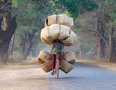 Uma mulher anda na sua bicicleta enquanto carrega cestos para vender no mercado em Myanmar.