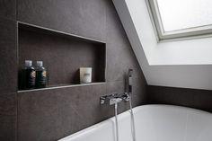 Grå skifferplattor på både väggar och golv. Under ett stort fönster i snedtaket står ett runt, fristående badkar med handdusch och förvaringsnisch. I badrummet finns även en dusch med takdusch och två glasdörrar, även den med en nisch för badrumsartiklar. Ett större vägghängt handfat med ett underrede i ljust trä kombineras med ett vägghängt badrumsskåp i samma serie. Alla rör i badrummet är infällda. Clawfoot Bathtub, Kitchen Lighting, Bathroom, Interior, Image, Washroom, Indoor, Full Bath, Interiors