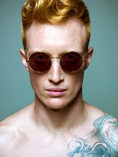 this guy sure rocks.  #redhead #freckles #sunglasses #tattoo #blue