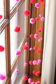 Thread pom poms onto lengths of transparent thread, knotted at the bottom, evenly spaced out.  Tape to the trim at the top of a window.