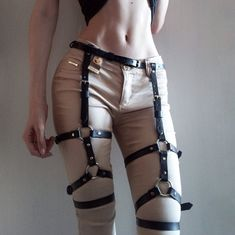 A leather leg harness - elegant garters that either could be  wear in addition to other fetish items or act as an independent and self-sustained accessory. Stockings tigtly fit body from waist, where all construction is attached to belt, to thigs, where straps mounted with iron rings grasp legs,making them visually more slimmer and graceful. In keeping with any style, erotic item either could be slightly hidden under skirt or dress, or can be worn over jeans or pants.  Due to large fasteners…