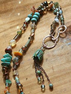 The copper flower bud was given a colorful patina and verdigris treatment. Small copper chains with glass beads dangle from its center. I then