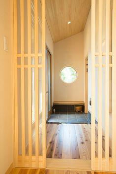 丸窓とベンチのある玄関土間。奥にはシューズクローゼットがあり、靴やアウトドアグッズを収納しています。 デザイン ナチュラル 