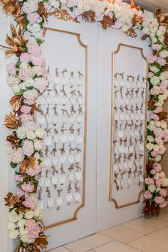 An arch of ivory and pink flowers with gold leaves framed the place card display. #WeddingDecor Photography: Amy & Stuart Photography. Read More: http://www.insideweddings.com/weddings/chic-white-blush-gold-seaside-wedding-at-montage-laguna-beach/676/
