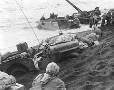 Jeep buried by surf in the sand of Iwo Jima Beach, 1945. Photographed by T/Sgt. H. Neil Gillespie.