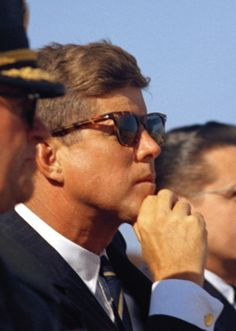 JFK wearing tortoiseshell sunglasses with a navy suit and club tie.