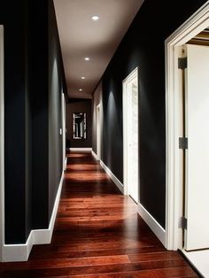 You would think that a long hallway painted black would be depressing and gloomy, but this hallway shows that it anything but. Crisp white doors and frames, white ceiling and white painted trim create Black Hallway, Long Hallway, Yellow Hallway, Black Rooms, Black Walls, Black Painted Walls, Bedroom Black, White Walls, Hallway Paint