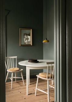 Green dining nook with neutral furnishings and simple artwork.