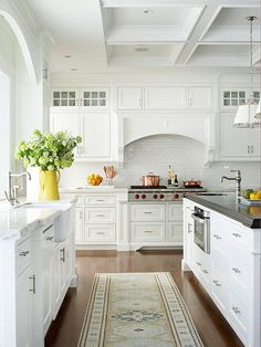 Elegant Cottage - This traditional, cottage-style kitchen is spacious, light, and airy with its all-white color palette. Custom cabinetry, Carrara marble perimeter countertops, and a coffered ceiling set a sophisticated tone. The rich, wooden floors add a warm, homey touch.