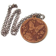 This pendant necklace is made with cherry wood. The round brownish red wood pendant has a butterfly flower and leaf pattern intricately laser cut into the surface.  The antiqued copper flat link chain matches beautifully with the pendant.  An absolutely gorgeous piece!