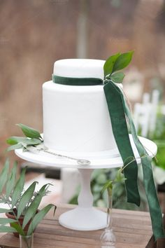 White cake decorated with green velvet ribbons and leaves with silver cake shovel on white stand and green and beige background - stock photo Snow White Cake, Silver Cake, Beige Background, White Candles, Velvet Ribbon, Green Velvet, Green Wedding, Vintage Silver, Green Colors