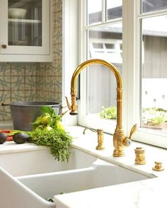 A large accordion-style folding window above the sink opens to an outdoor countertop serving and dining area. Countertops in the kitchen are Calacatta marble. - Photo: John Merkl / Design: Cecily Mendell