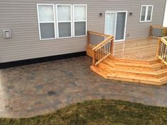 Project finished up with the corner wrap around steps on the cedar deck. Oaks Colonnade brick paver patio in the sandelwood color with double border a… - All About Garden
