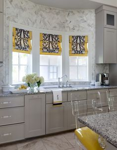 Tobi Fairley designed gray and yellow kitchen, gray cabinets and marble subway tile in a herringbone installation.