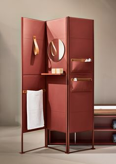 SHADE is a folding screen offering an upscale solution to maximize the bathroom space. It is possible to accessorize it with shelves, leather loop towel holders, mirrors, and object holder pockets. Here displayed in the exquisite medium grain red leather.