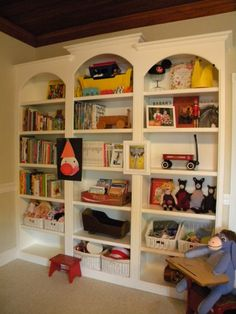 take inexensive ikea bookshelves & beef up with molding, arches, etc...