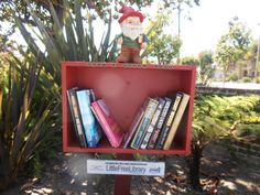 "Elizabeth Borsting. Long Beach, CA. My husband found the Library, painted it and found the gnome holding a book. I added typewriter-style letters beneath that said ""What a Novel Idea"" to describe the Little Free Library movement. My 10 year old daughter loves to read and gets excited when books are dropped off. My 15 year old son is starting to come around and like it, too. Our 4 year old Jack Russell Terrier loves it when people are browsing through the library. She greets them with a bark!"
