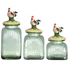 Three glass jars with rooster finials.Product: Small, medium and large jarConstruction Material: Polyresin and glassFeatures: Will enhance any dcor Dimensions: Small: H x WMedium: H x WLarge: H x WNote: Not recommended for outdoor use Storage Canisters, Glass Canisters, Kitchen Canisters, Glass Jars, Kitchen Storage, Clear Glass, Vintage Canisters, Kitchen Counters, Kitchenware