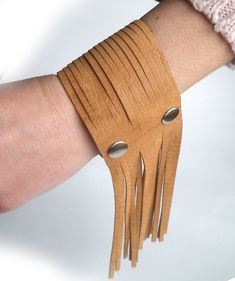 Real leather bracelet made of leather in colour camel. With fringe. Closure with snapping two metal snaps. Easy and comfortable to snap on wrist. Comfortable, soft, not scratching your skin. Made very carefully. After closure, the bracelet is suitable for wrist circumference ca.15cm (6 inches). Width: 5,5cm (2,25 inches). If you need other size – don't hesitate to ask. Attached label of designer.