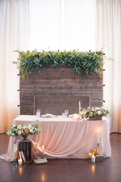 a barnwood backdrop with lush greneery on top and lights on its sides